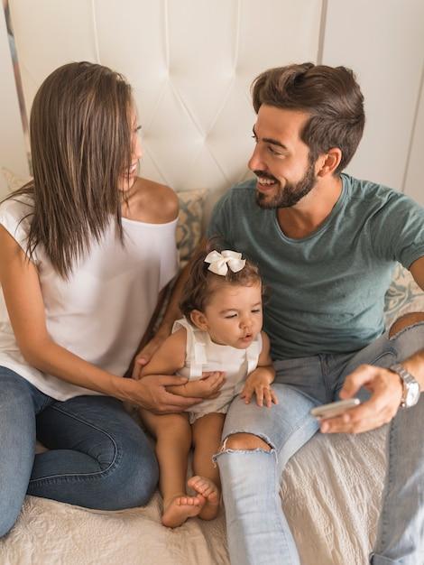Jovens, com, bebê, e, smartphone, olhando um ao outro Foto gratuita