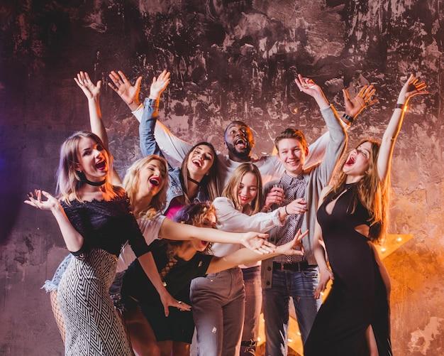 Jovens comemorando amigos com as mãos para cima Foto gratuita