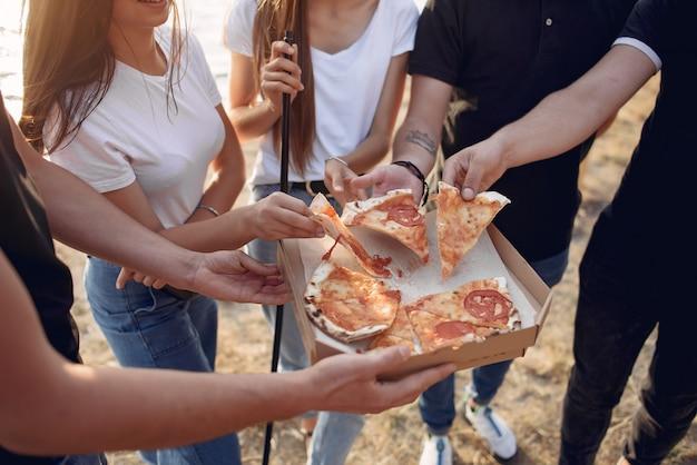 Jovens comendo pizza e fumando shisha na praia Foto gratuita