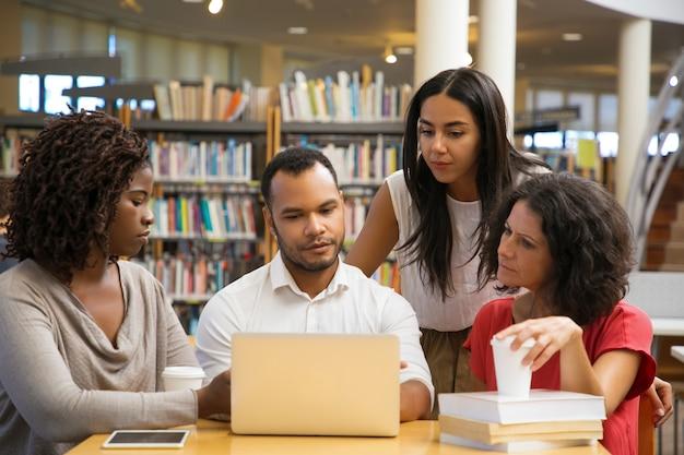 Jovens concentrados lendo informações do laptop Foto gratuita
