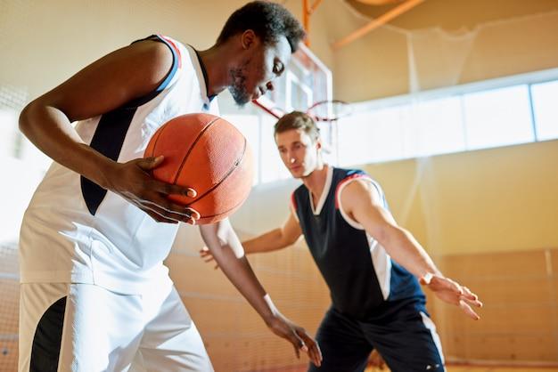 Jovens concorrentes jogando basquete na quadra de treinamento Foto Premium