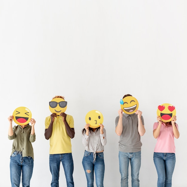 Jovens de cópia-espaço cobrindo cabeças com emoji Foto gratuita