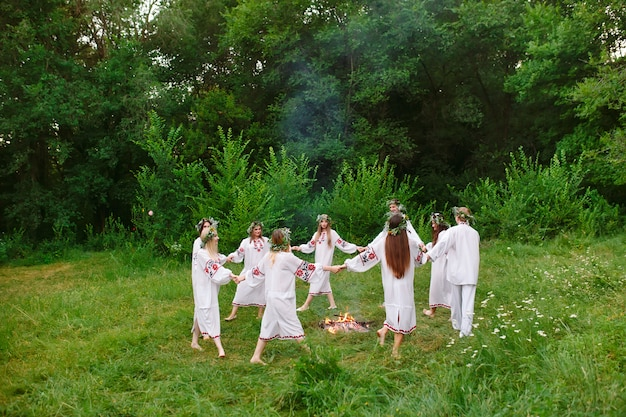 Jovens em roupas eslavas giram em torno de um incêndio no verão. Foto Premium
