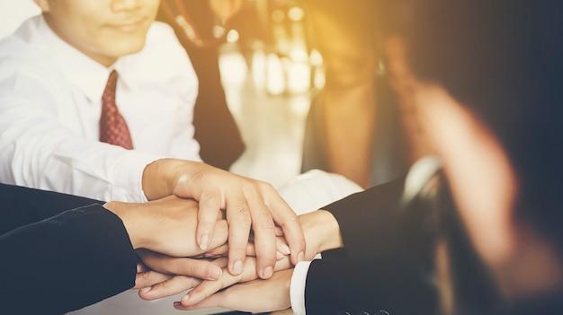 Jovens empresários juntam as mãos para fazer negócios juntos pela união em equipe. Foto Premium