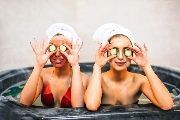 Jovens engraçadas sentam-se no banho de hidromassagem e seguram pedaços de pepino nos olhos. eles têm procedimentos de beleza e spa no quarto. modelos parecem felizes. Foto Premium