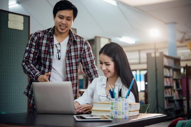 Jovens estudantes aprendendo, estantes de biblioteca Foto gratuita