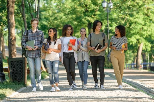 Jovens estudantes felizes andando enquanto fala Foto gratuita