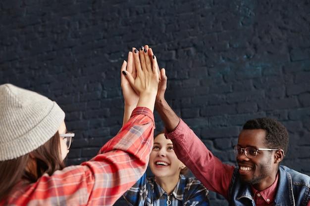 Jovens felizes dando mais cinco tapa uns aos outros entregam parabéns durante reunião no café. empreendedores criativos em roupas informais rindo e comemorando o sucesso do projeto de arranque Foto gratuita