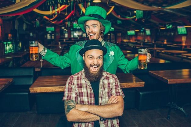 Jovens felizes e animados ficar no bar e posar. cara na frente, mantenha as mãos cruzadas e sorria. jovem por trás usar terno verde e tem duas canecas de cerveja. Foto Premium
