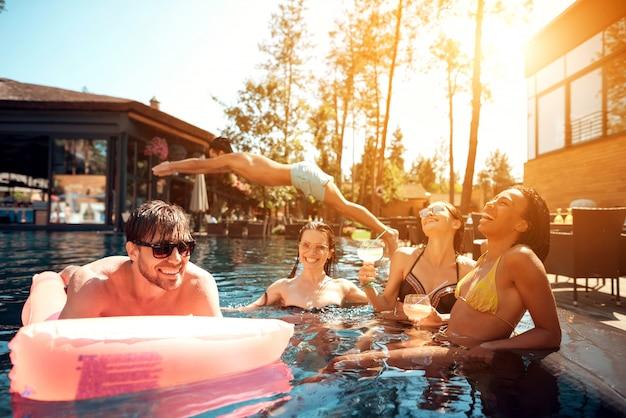 Jovens felizes nadando na piscina Foto Premium