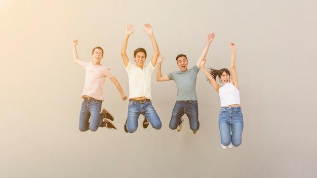 Jovens felizes pulando juntos Foto gratuita