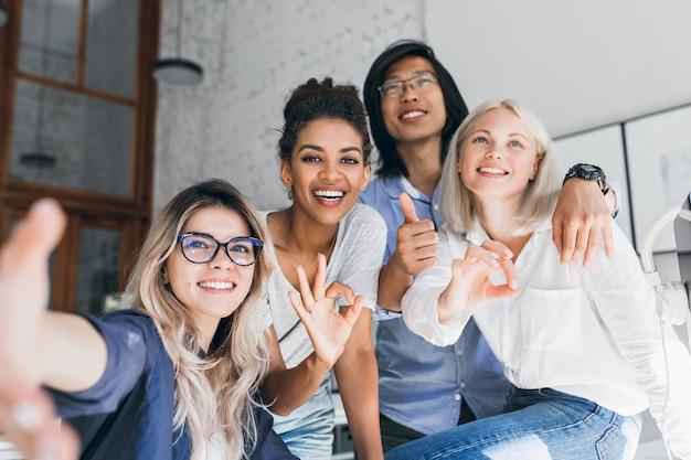 Jovens funcionários de escritórios internacionais posando juntos e rindo durante o intervalo Foto gratuita