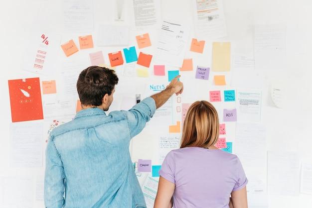 Jovens funcionários olhando para parede com notas de marketing Foto gratuita