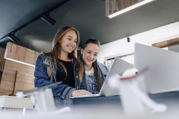 Jovens garotas atraentes em uma loja de eletrônicos usam um laptop em uma exposição. conceito de compra de gadgets. Foto gratuita