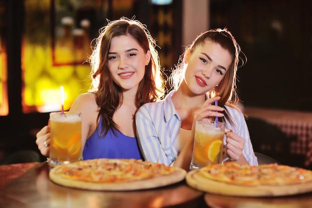 Jovens garotas bonitas comem pizza e bebem cerveja ou um coquetel de cerveja em um bar ou pizzaria Foto Premium