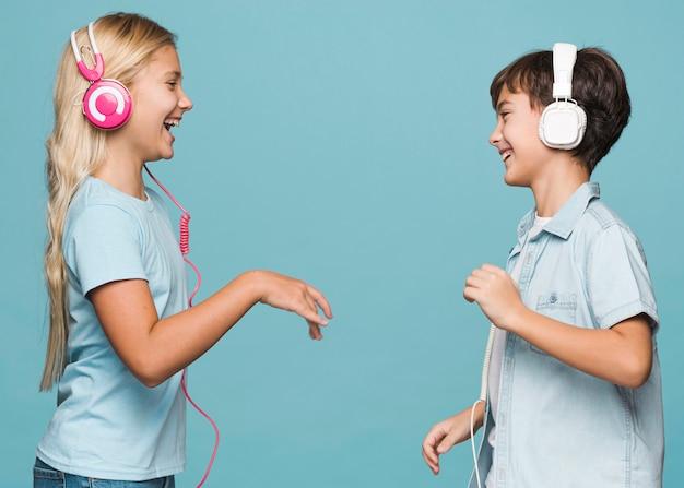 Jovens irmãos ouvindo música Foto gratuita