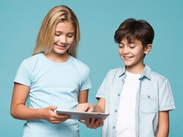 Jovens irmãos usando tablet juntos Foto gratuita