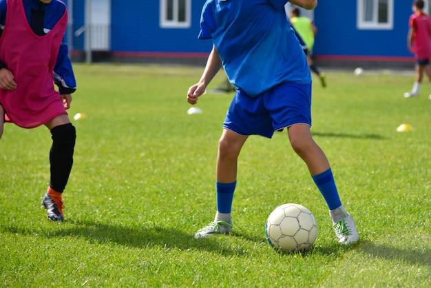 Jovens jogadores de futebol jogam futebol no treinamento Foto Premium