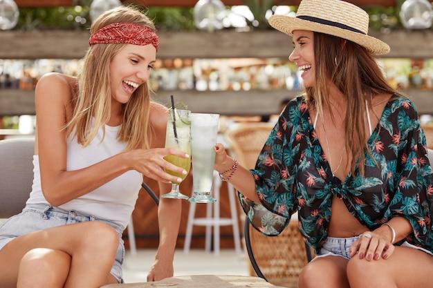 Jovens lindas e cheias de alegria fazem a festa de verão juntas, brindam com copos de coquetéis, desfrutam de boas recreações e conversam agradáveis. melhores amigos alegres bebem bebidas de verão. hora de relaxar Foto gratuita