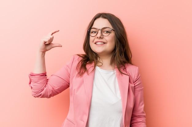 Jovens mais mulher caucasiana de negócios de tamanho segurando algo pouco com o dedo indicador, sorrindo e confiante. Foto Premium