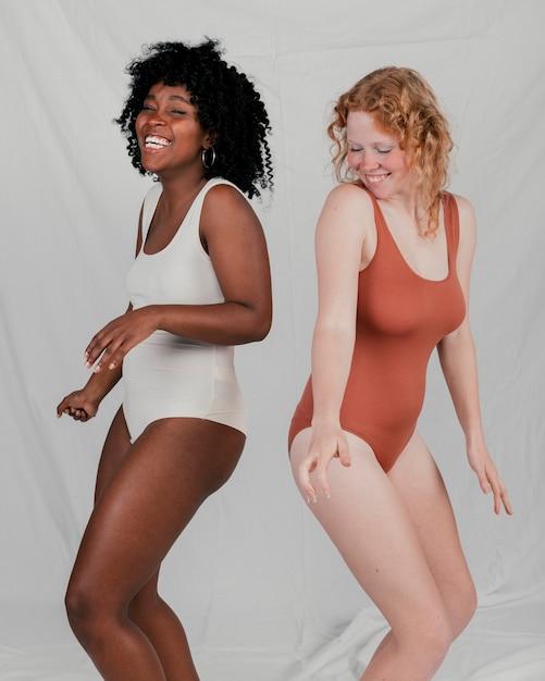 Jovens mulheres africanas e loiras dançando contra pano de fundo cinzento Foto gratuita