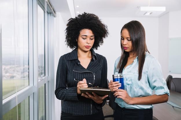 Jovens mulheres americanas africanas com copo de vácuo e documentos perto da janela Foto gratuita