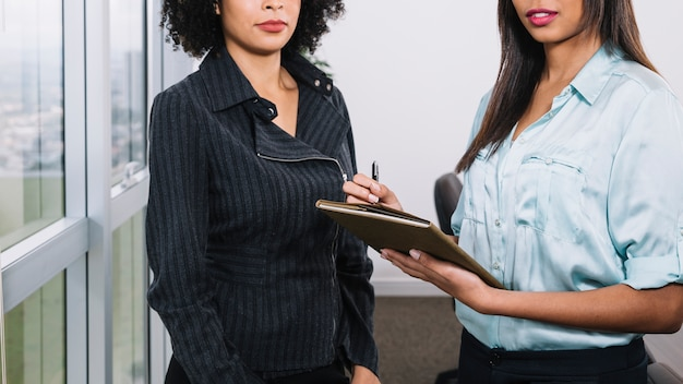 Jovens mulheres americanas africanas com documentos perto da janela Foto gratuita