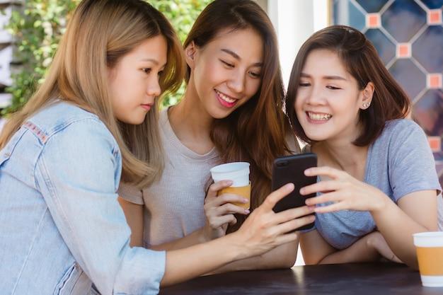 Jovens mulheres asiáticas alegres que sentam-se no café que bebe o café com amigos e que falam junto Foto gratuita