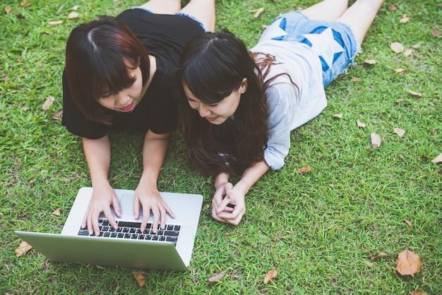 Jovens mulheres asiáticas pernas na grama verde com laptop aberto Foto Premium