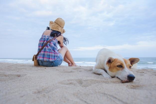 Jovens mulheres asiáticas sente-se tristemente na praia à beira-mar com um cachorro, sentado na praia ao fundo Foto Premium
