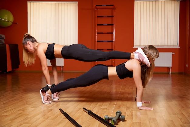 Jovens mulheres atléticas um treinamento no gym. Foto Premium