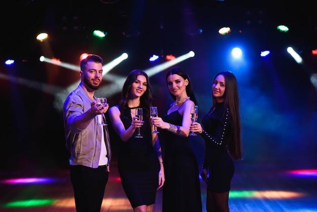 Jovens mulheres atraentes e homem comemorando uma festa, bebendo champanhe e dançar Foto Premium