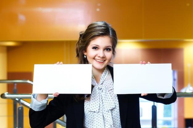 Jovens mulheres bonitas segurando dois cartão branco em branco Foto Premium