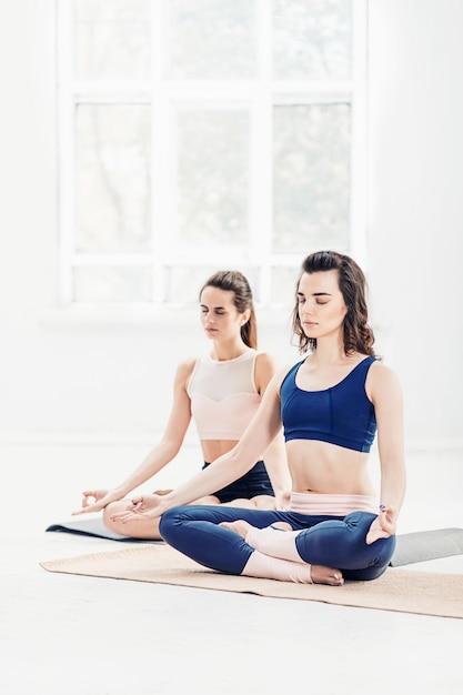 Jovens mulheres fazendo exercícios de ioga Foto gratuita