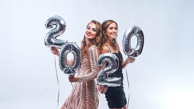 Jovens mulheres felizes com os balões 2020 metálicos no branco. Foto Premium