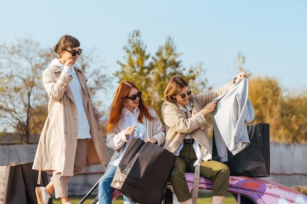 Jovens mulheres felizes com sacolas de compras se passando perto de um velho carro decorado Foto gratuita