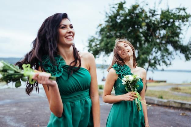 Jovens mulheres felizes em um casamento com buquês de flores Foto Premium