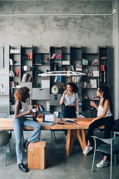Jovens mulheres multirraciais que têm a reunião informal no escritório moderno do co-working Foto Premium