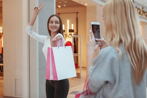 Jovens mulheres que apreciam fazer compras juntos no shopping Foto Premium
