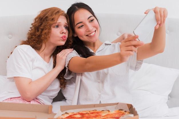 Jovens mulheres tomando selfie enquanto come pizza Foto gratuita