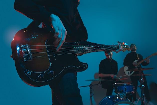 Jovens músicos caucasianos, banda tocando luz de neon no studio azul Foto gratuita