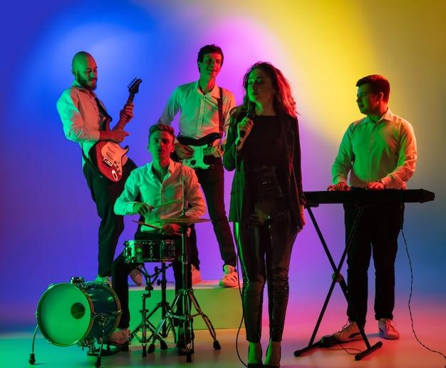 Jovens músicos caucasianos, banda tocando, tocando no espaço gradiente na luz de neon. conceito de música, passatempo, festival Foto gratuita