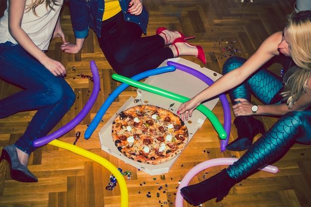 Jovens na festa de pizza Foto gratuita