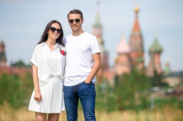 Jovens namoro casal apaixonado andando no fundo da cidade st basils church Foto Premium
