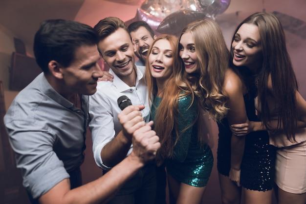 Jovens no clube dançam e cantam. Foto Premium