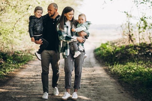 Jovens pais com seus filhos na floresta Foto gratuita