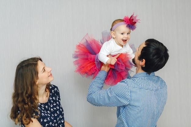 Jovens pais com sua linda filhinha em roupas de férias brilhantes e coroa artesanal Foto Premium