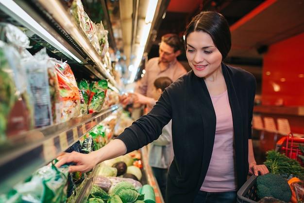 Jovens pais e filha na mercearia. mulher na frente picj ervas. pai e filha ficam atrás e conversam. Foto Premium