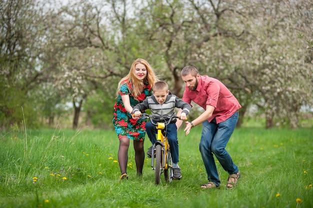 Jovens pais ensinando seu filho a andar de bicicleta Foto Premium