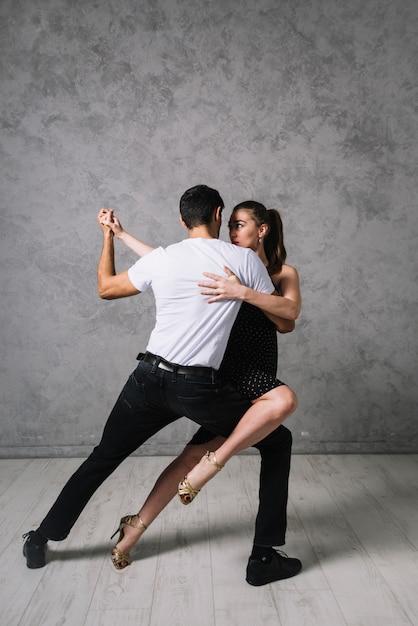 Jovens parceiros de dança dançando tango Foto gratuita